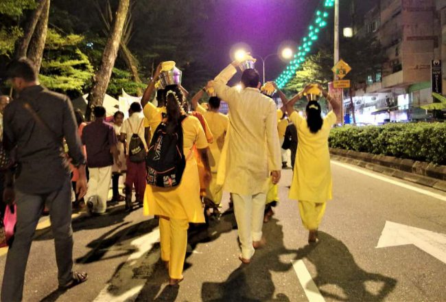 ヒンドゥ―教の奇祭タイプ―サムでミルクが入った壺を担ぎはだしでムルガンの寺院をめざす信者たちの写真